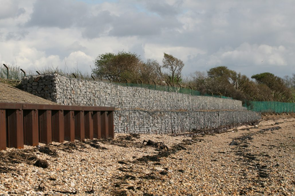 Coastal erosion defences in the form of interlocking concrete blocks in the foreground and stone-filled wired gabion baskets behind
