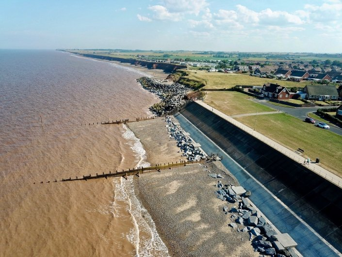 Downdrift of the sea defences at Withernsea , the adjacent undefended coast is being eroded resulting in a set back.