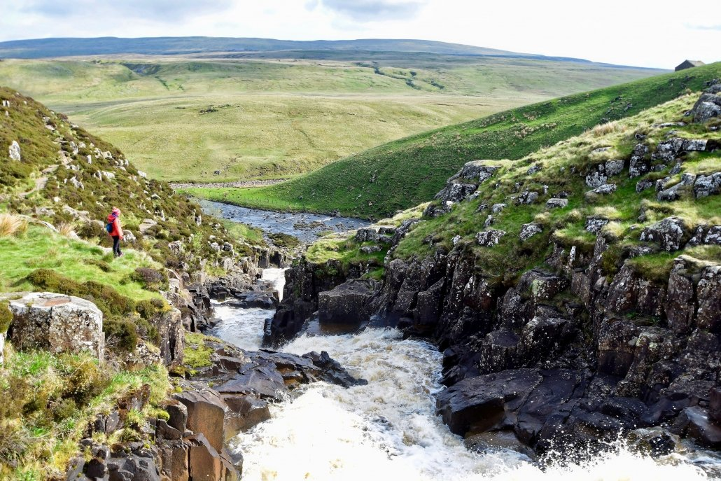 The upper course of a river with rapids as the river flows through steep V-shaped valleys.