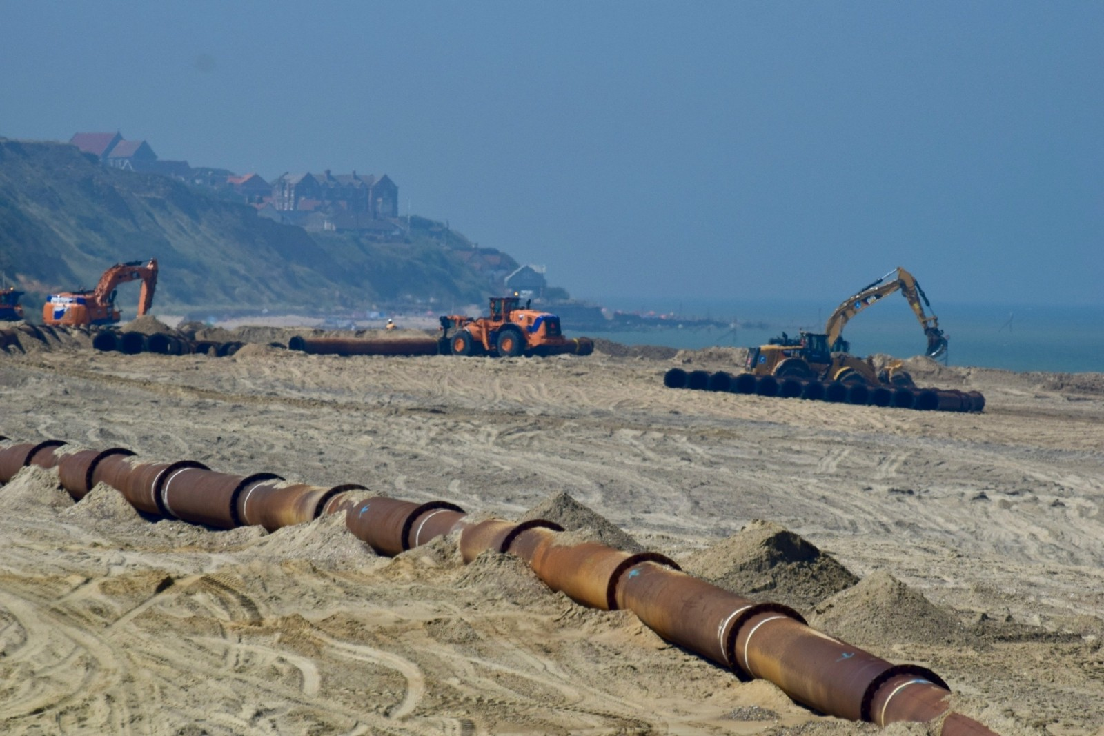 Sediment pumped onto the beach is moved by heavy machinery