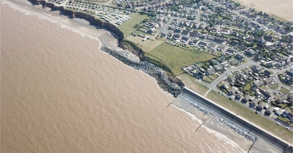 Impact of erosion down drift of defences
