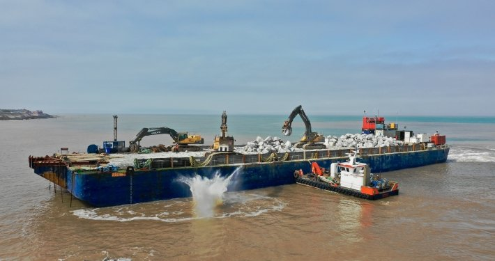 Rock being dropped from a barge
